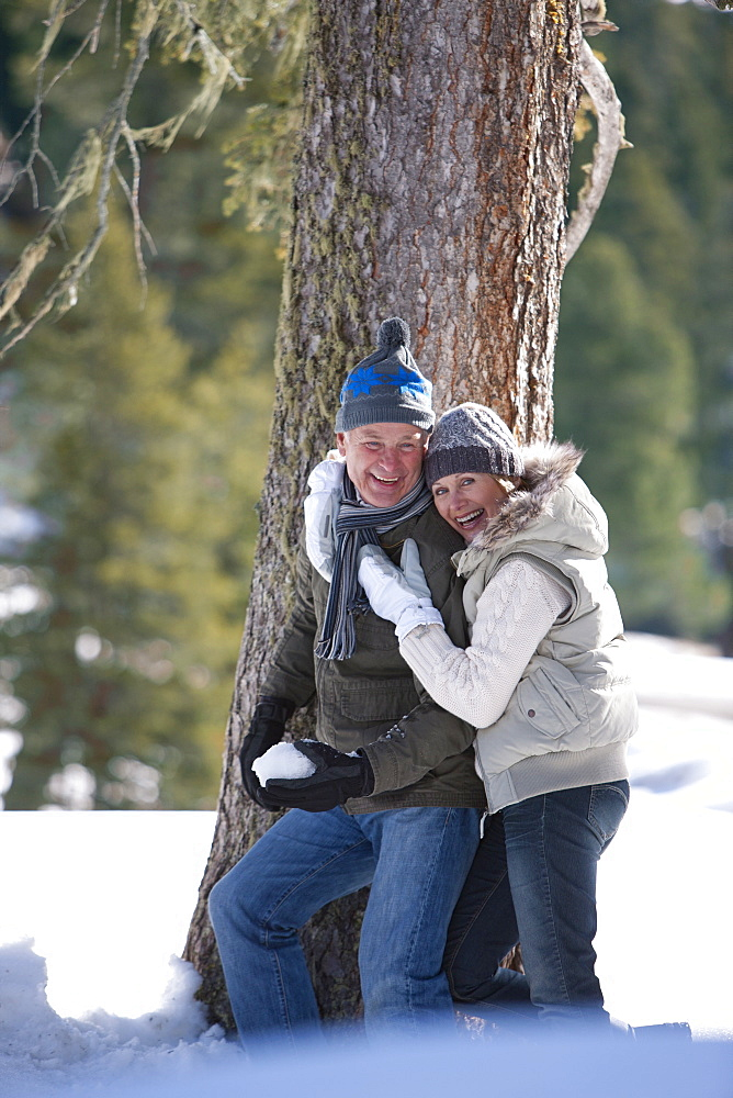 Couple hugging near tree outdoors in snow