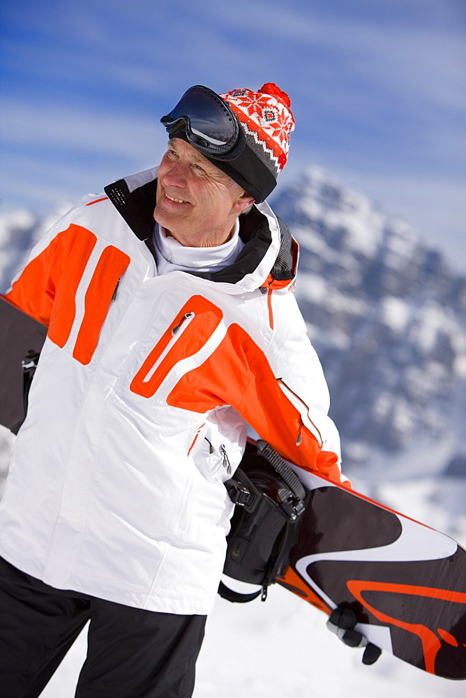 Smiling man holding snowboard