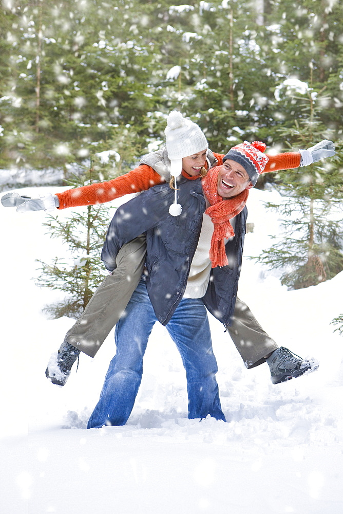 Man carrying exuberant woman on back in snowy woods