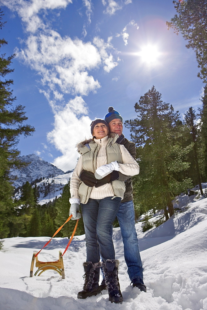Happy senior couple with sled hugging in snowy, sunny woods