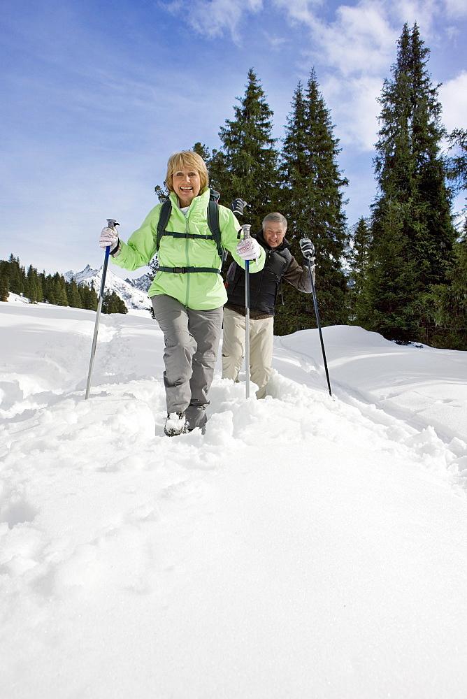 Senior couple walking in snow with ski poles