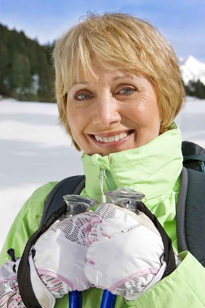 Close up portrait of woman holding ski poles