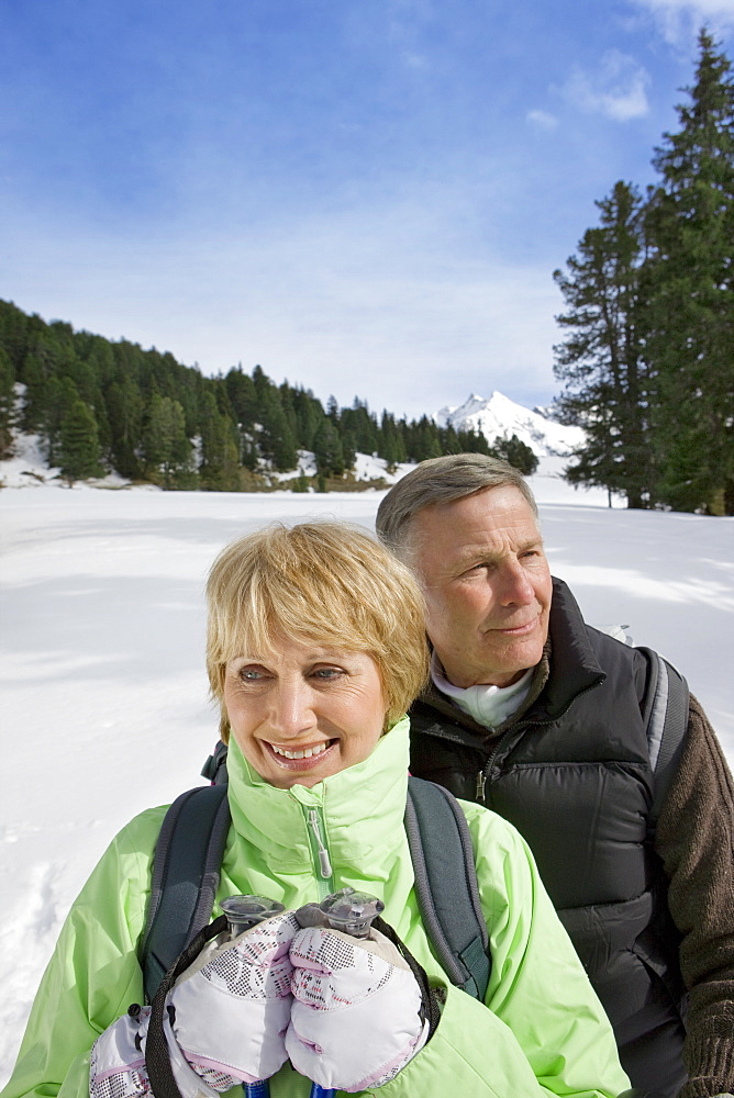 Senior couple standing in snow with mountain in background