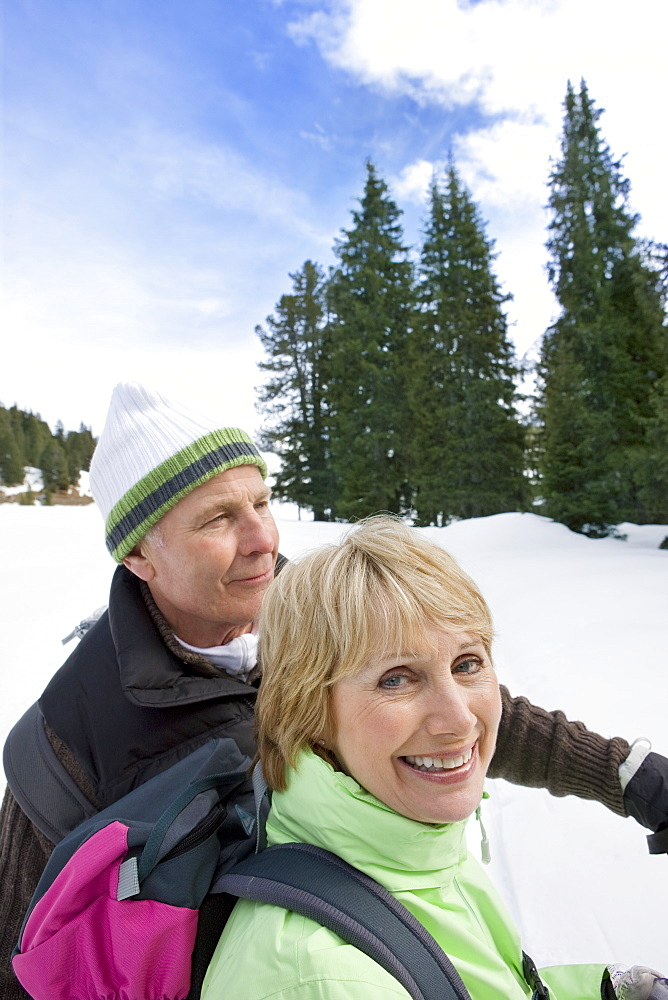 Close up of happy senior couple backpacking in snowy woods
