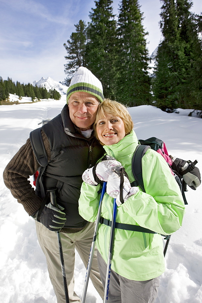 Portrait of happy senior couple backpacking with ski poles in snow