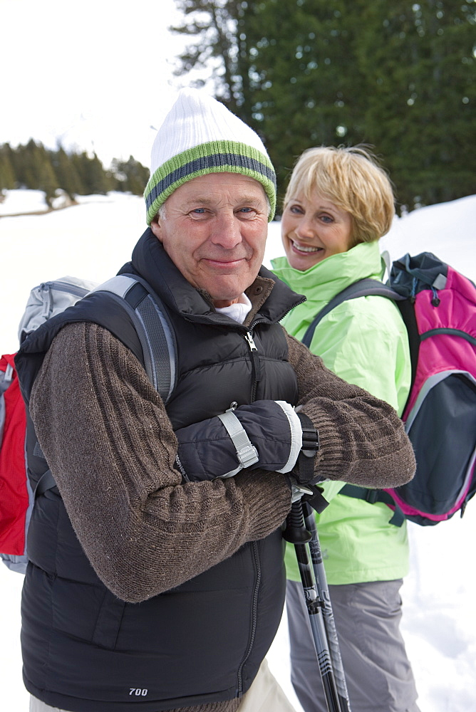 Portrait of senior couple with backpacks and ski poles in snowy woods