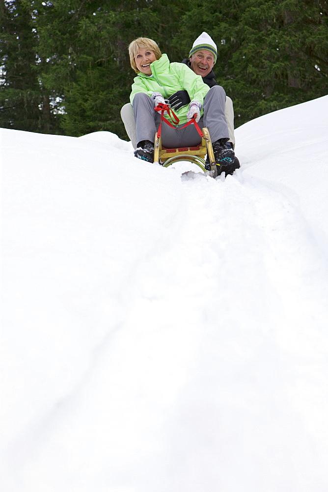Happy senior couple sledding down snowy slope