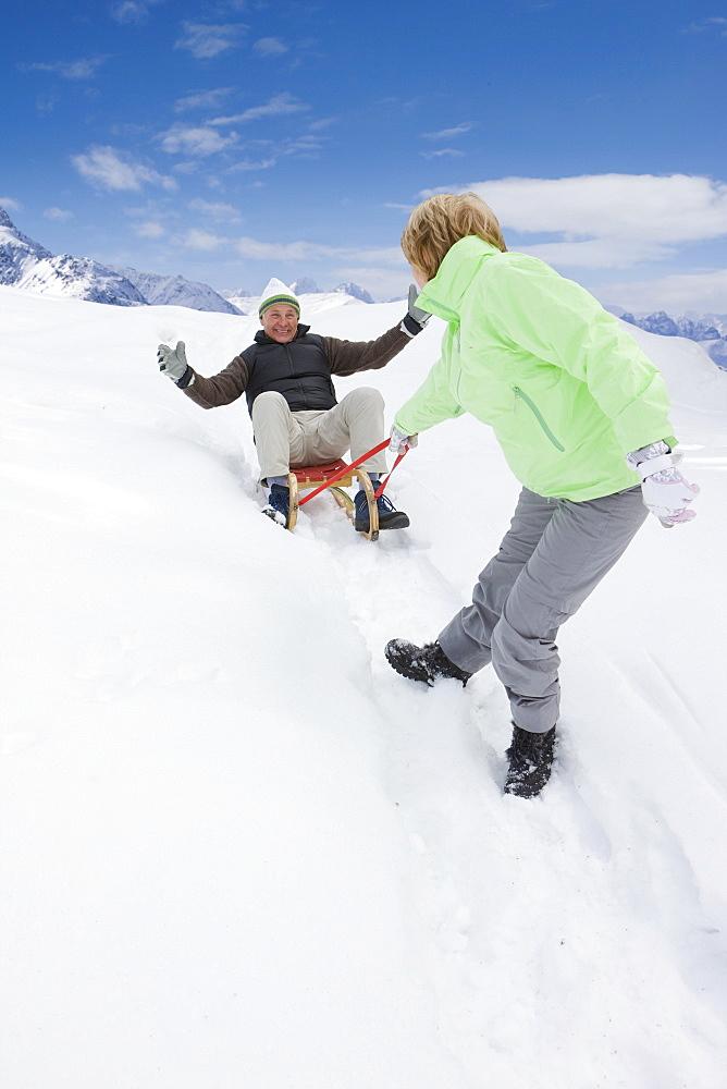 Playful senior couple sledding down snowy slope
