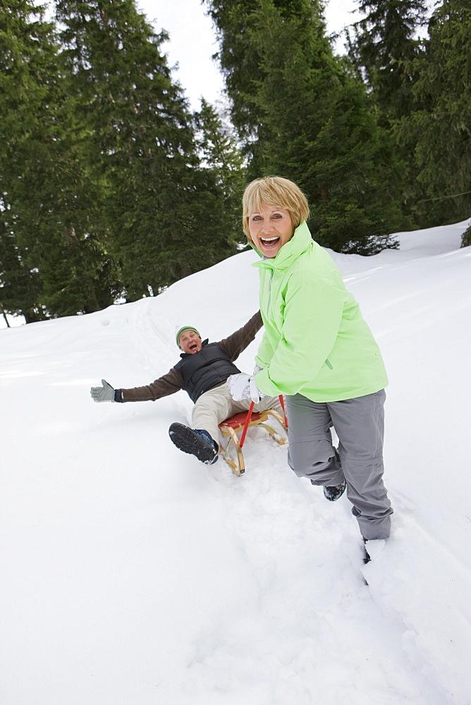 Portrait of playful senior couple sledding in snowy woods