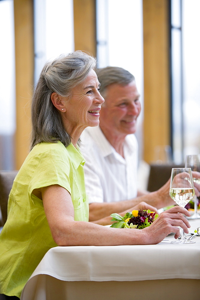 Couple eating salad and drinking white wine at restaurant table