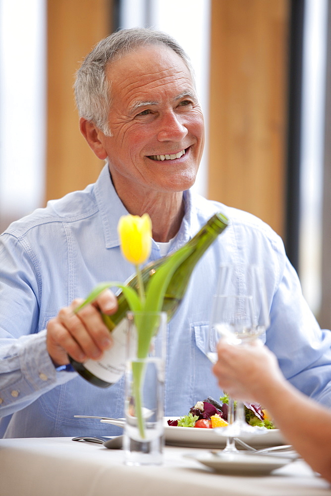 Happy man pouring white wine for woman at restaurant table