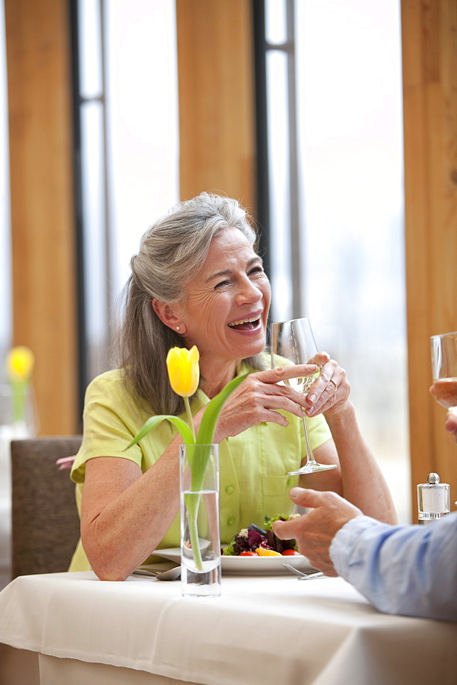 Happy couple drinking white wine at restaurant table