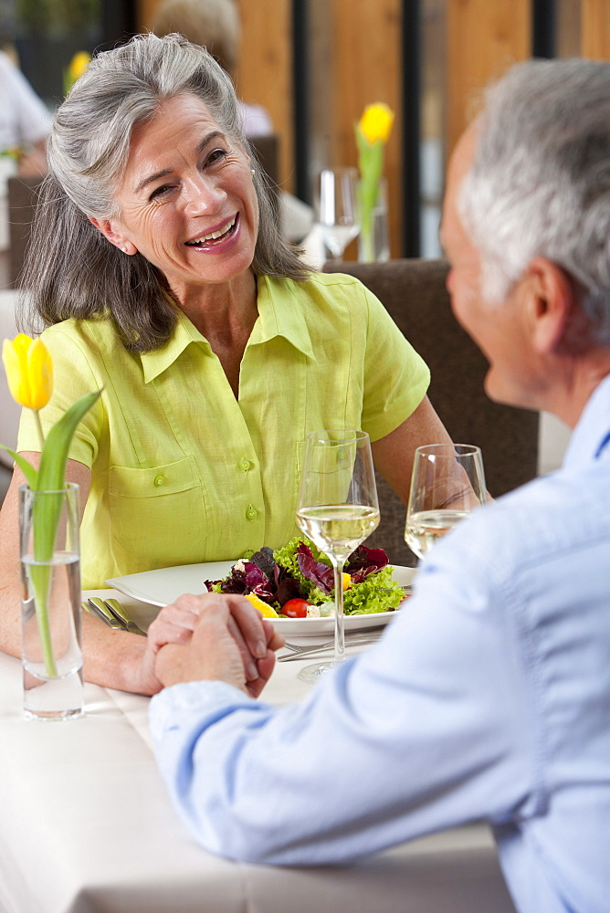 Happy senior couple holding hands at restaurant table