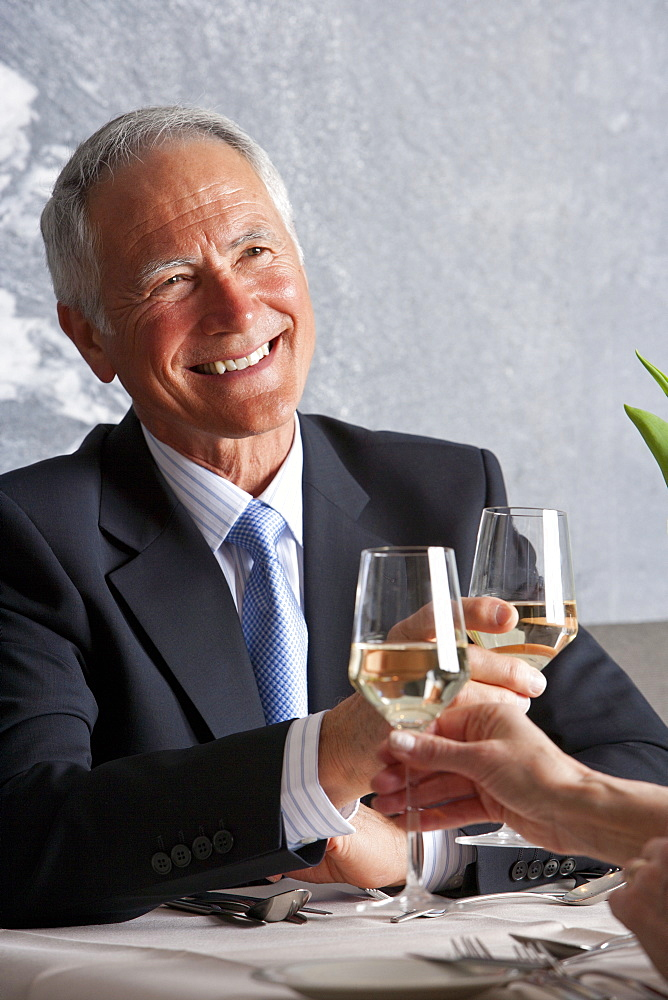 Happy well-dressed senior couple toasting wine glasses at restaurant table