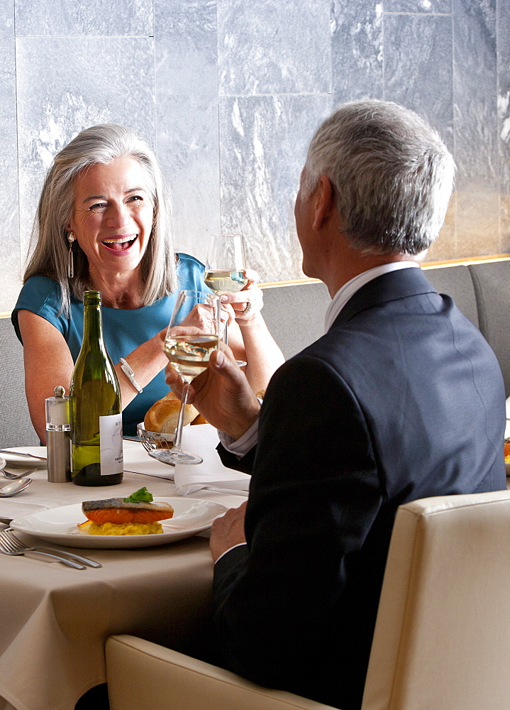 Happy, well-dressed couple dining at restaurant table