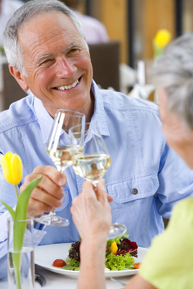 Happy couple toasting wine glasses at restaurant