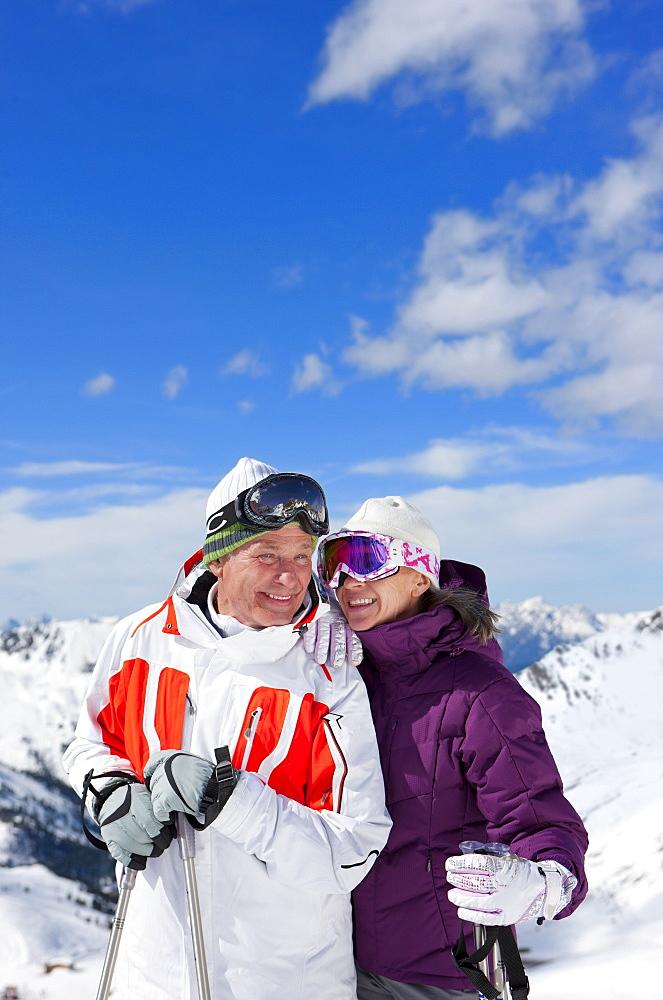 Smiling couple with ski poles on snowy mountain