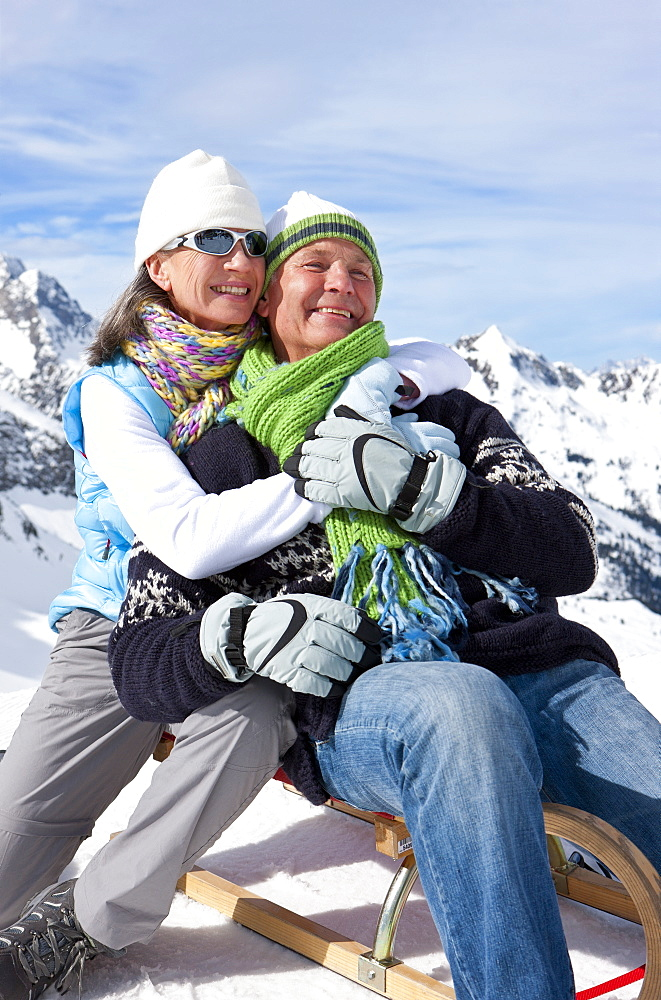 Smiling couple hugging on sled on snowy mountain