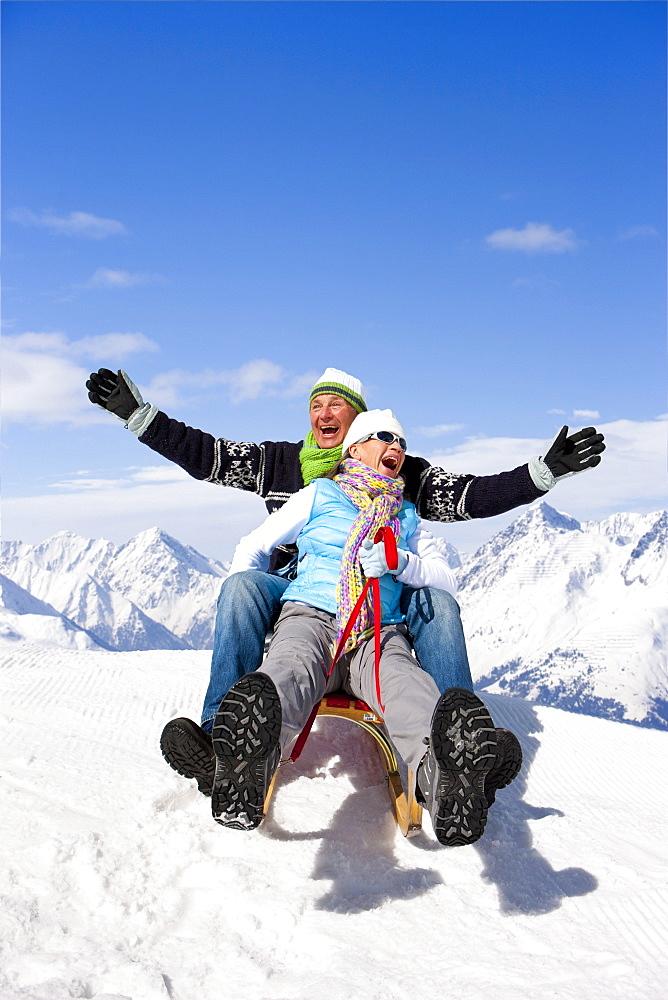 Enthusiastic couple sledding on snowy mountain