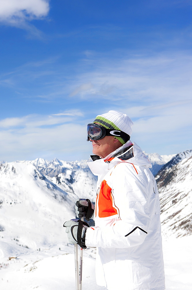 Smiling man wearing ski goggles and holding ski poles on snowy mountain