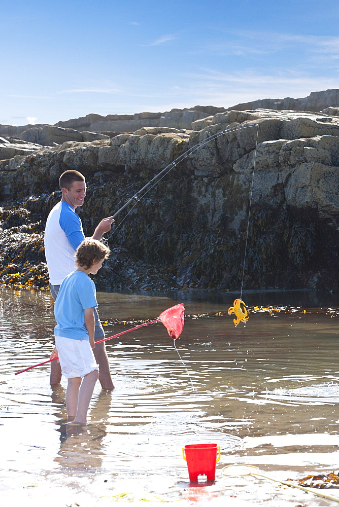 Father and son fishing in tide pool