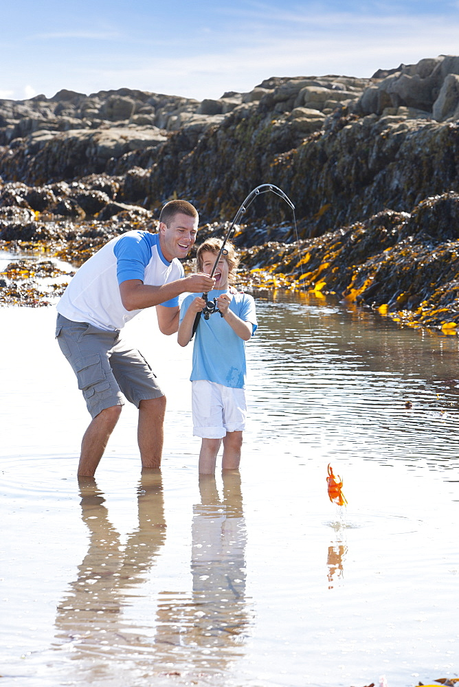 Father and son catching crab with fishing rod in tide pool