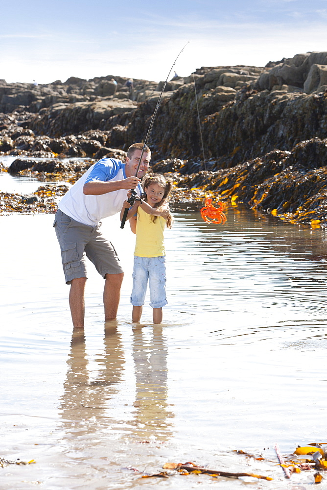 Father and daughter catching crab with fishing rod in tide pool