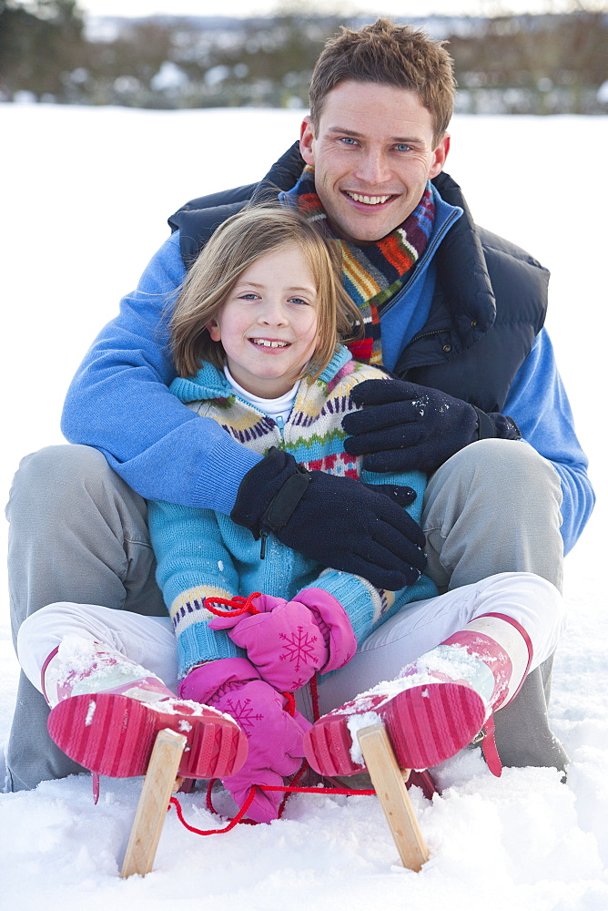 Portrait of smiling father and daughter sitting in snow