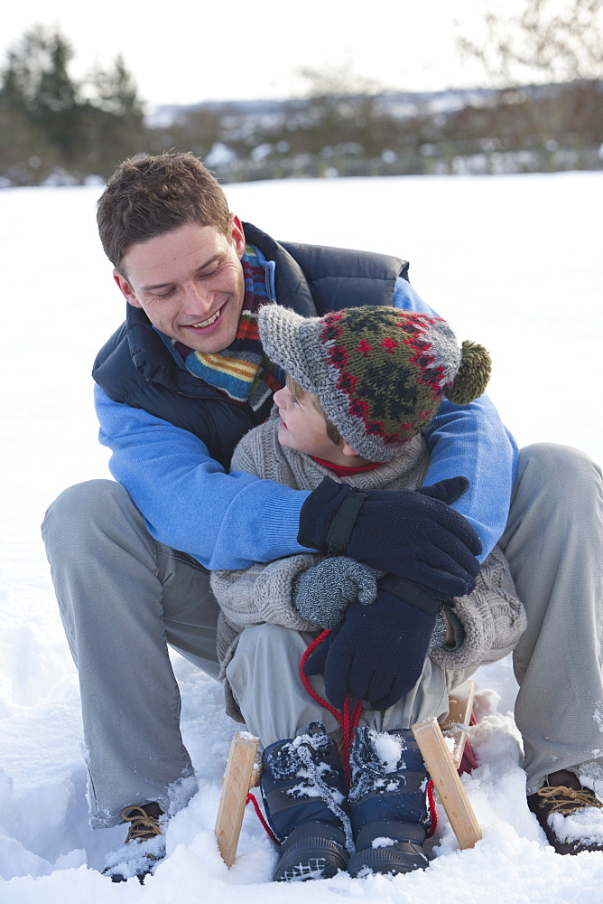 Father and son sitting on sled and hugging in snow