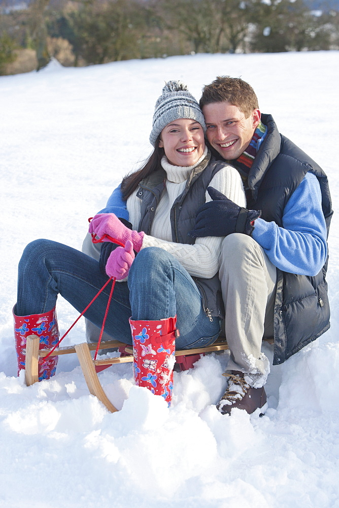 Portrait of smiling couple sitting on sled and hugging in snow