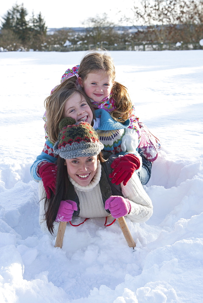 Portrait of smiling mother and daughters laying on sled in snow