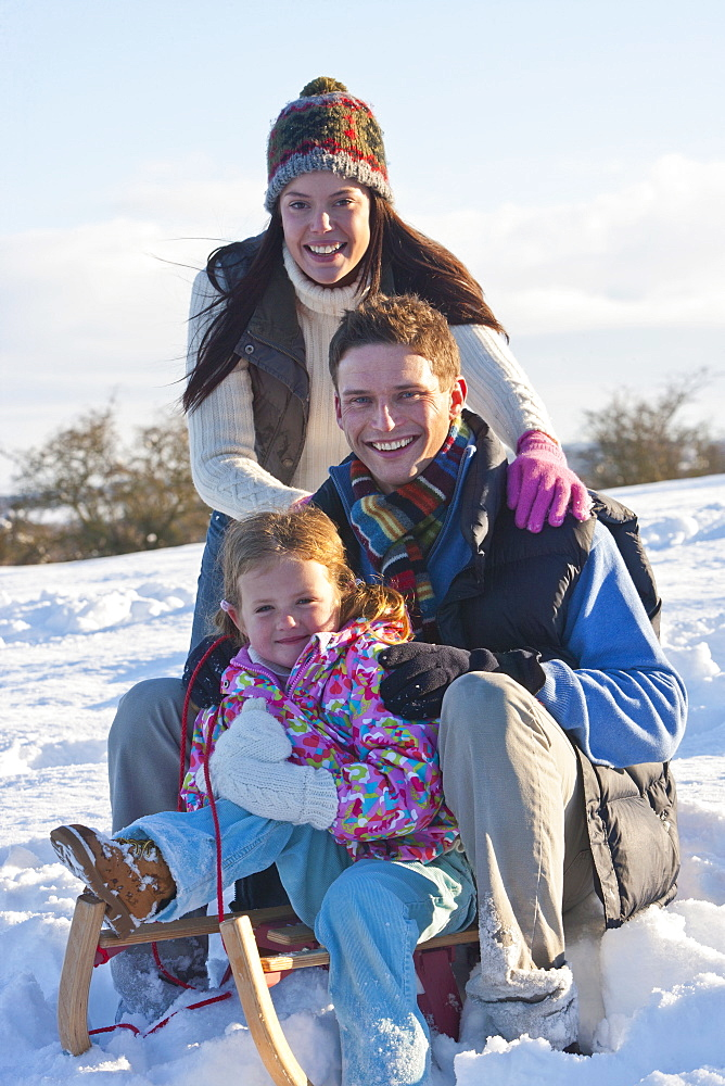 Portrait of smiling family with sled in snow