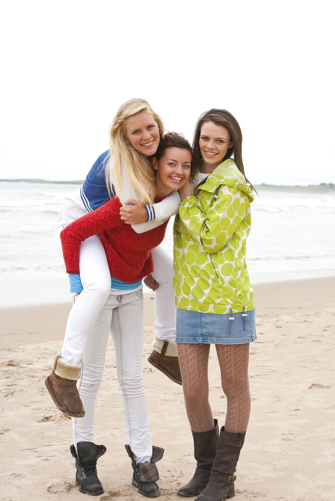 Portrait of smiling young women piggybacking on beach