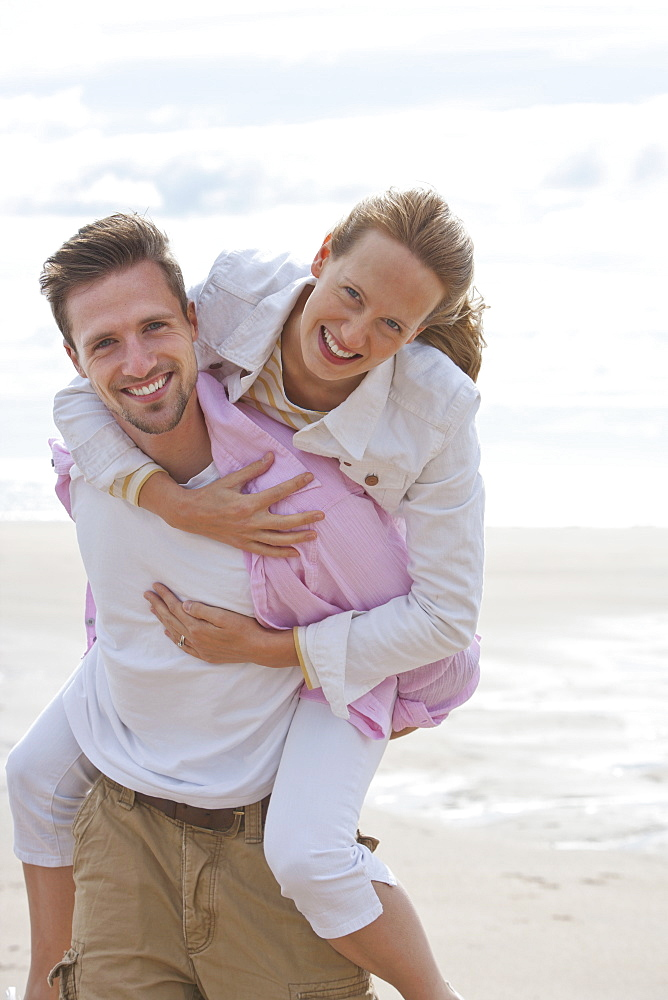 Portrait of smiling young couple piggybacking on sunny beach