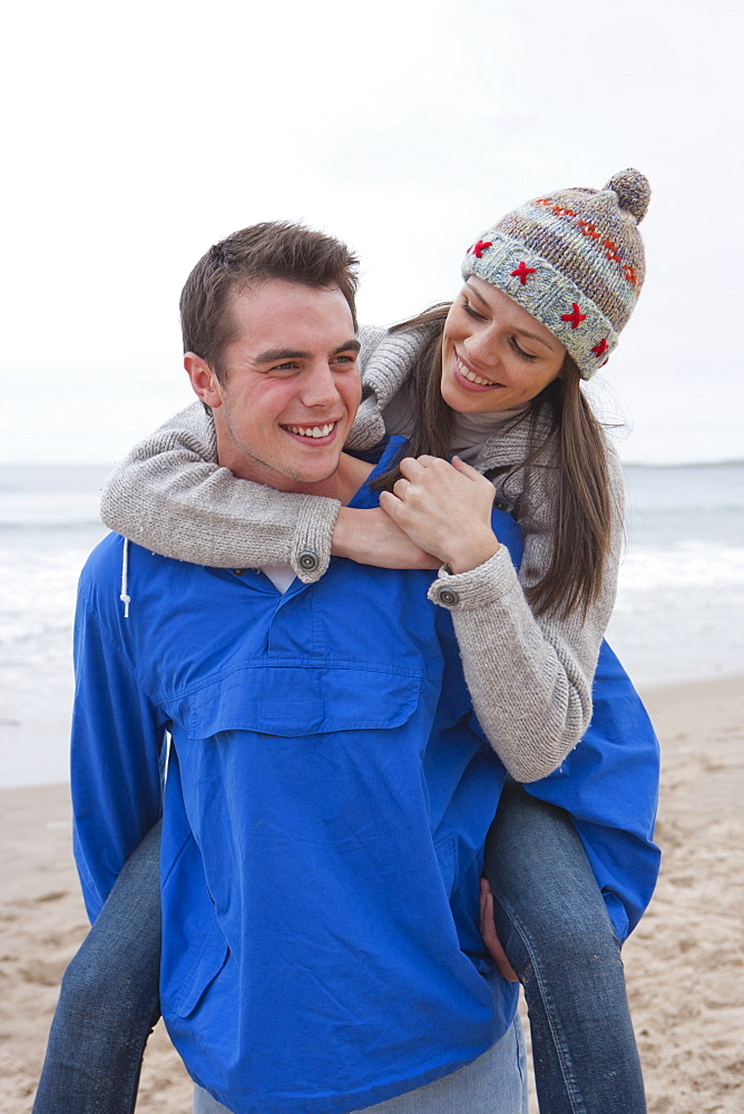 Young couple piggybacking on beach