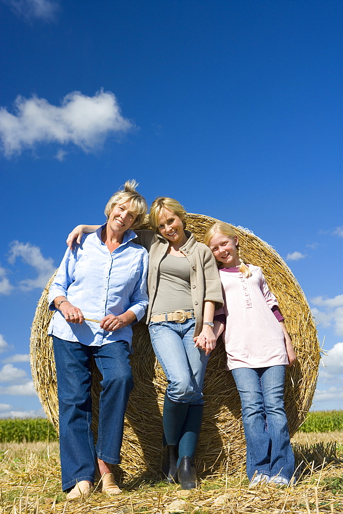 Family of three generations of women by bale of hay in field, smiling, portrait, low angle view
