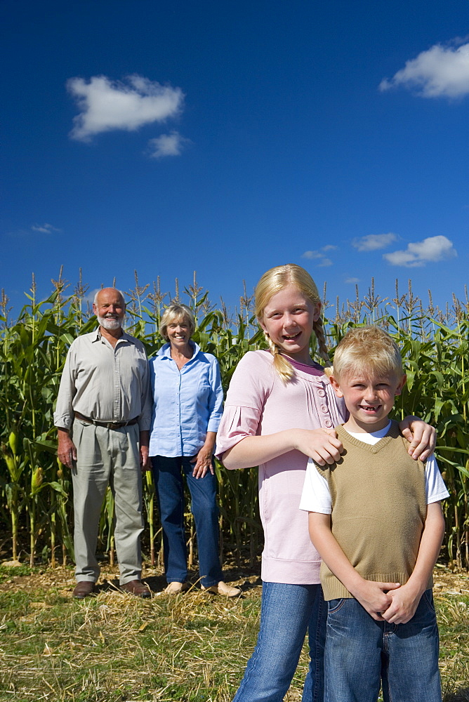 Brother and sister (7-11) by corn field, grandparents in background, smiling, portrait, low angle view