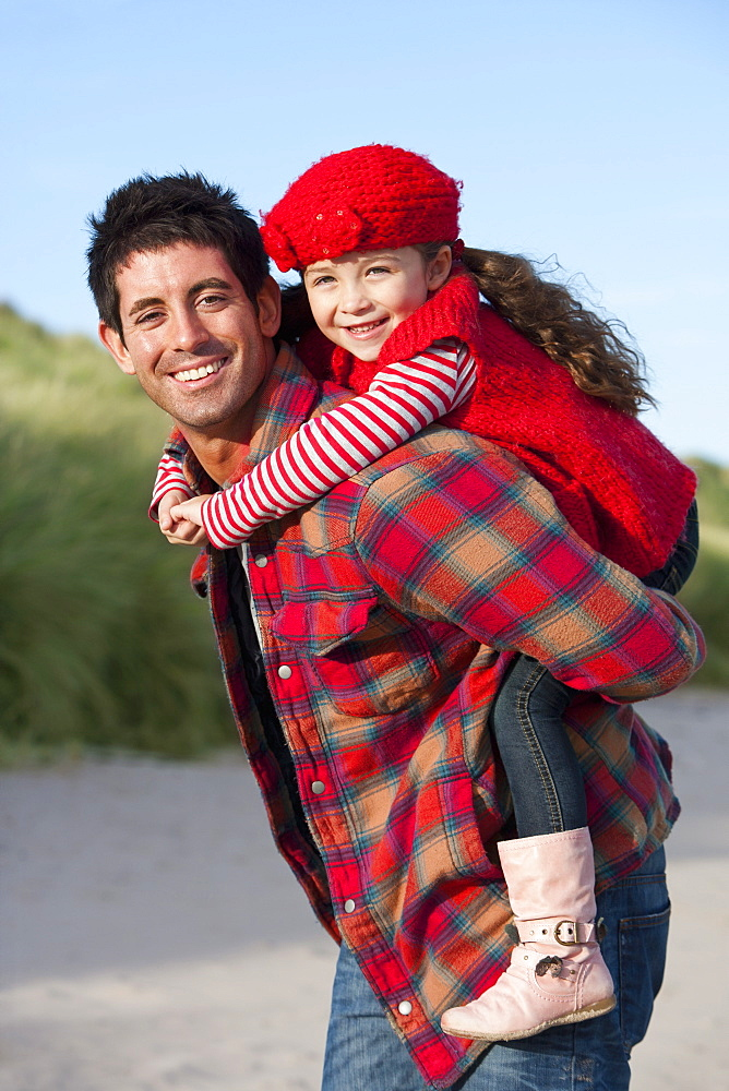 Portrait of smiling father piggybacking daughter on beach