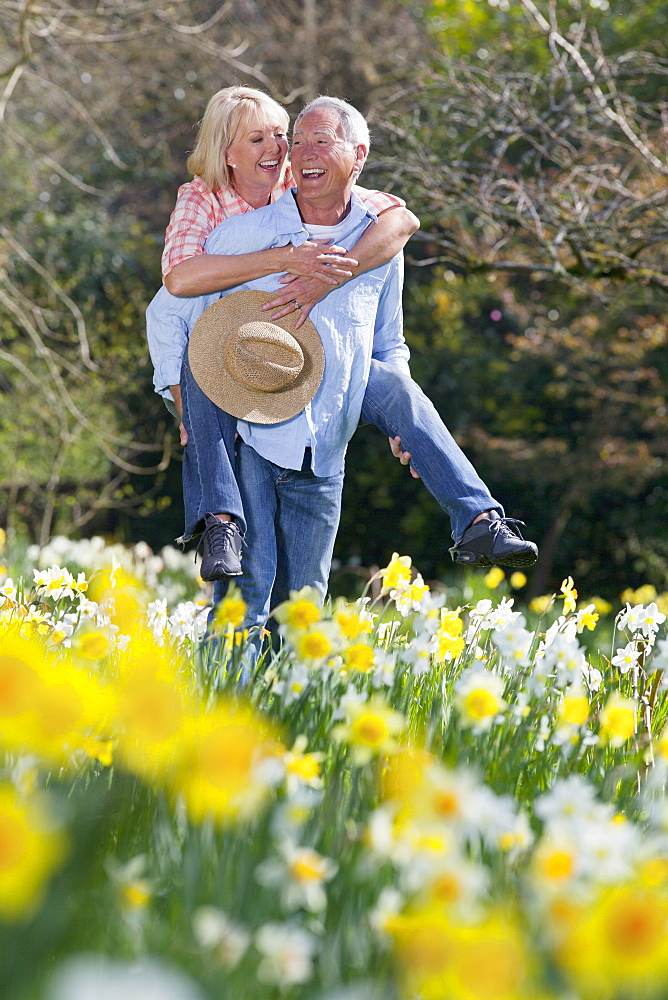 Smiling senior couple piggybacking in sunny daffodil field