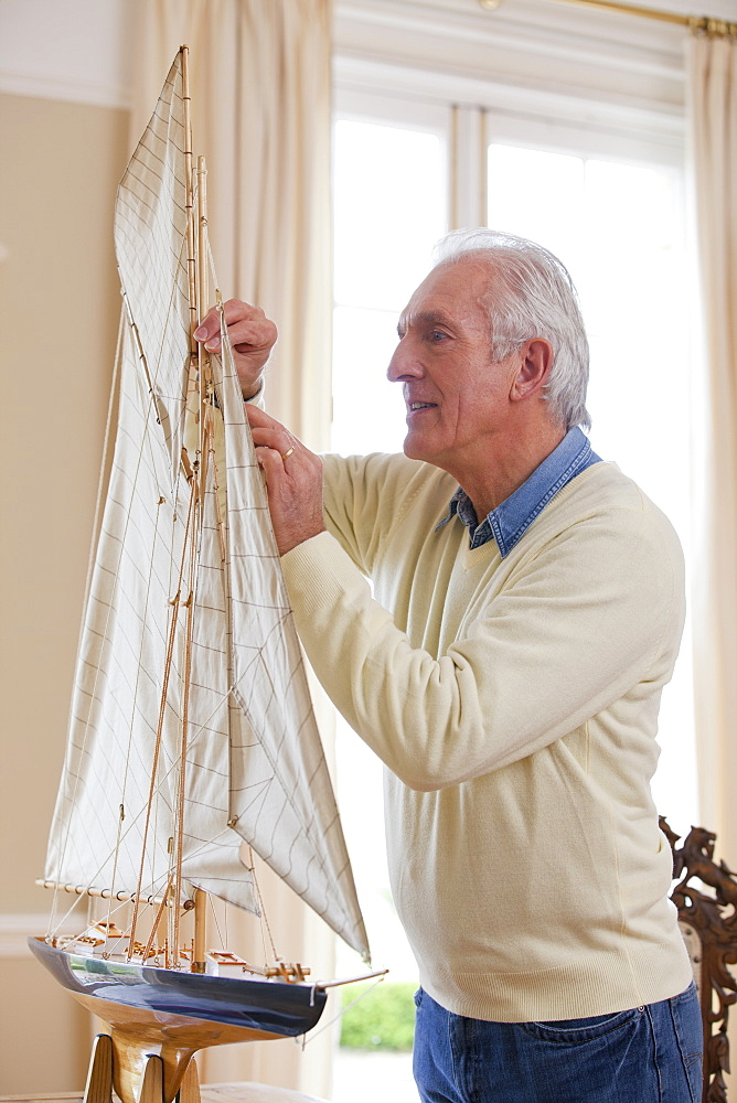 Senior man assembling model sailboat