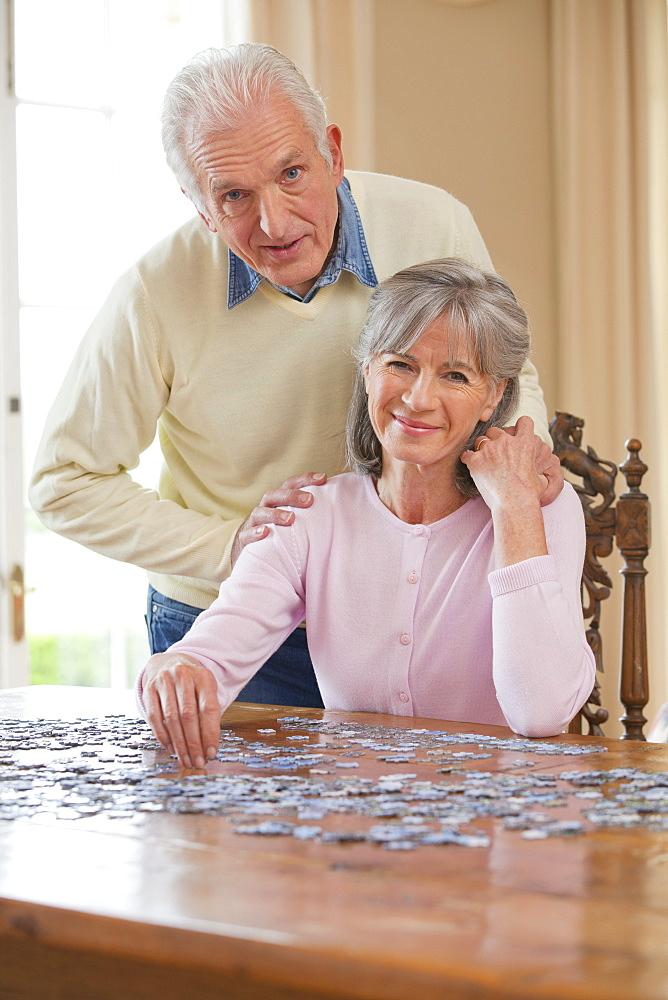 Portrait of smiling senior senior couple assembling jigsaw puzzle on table