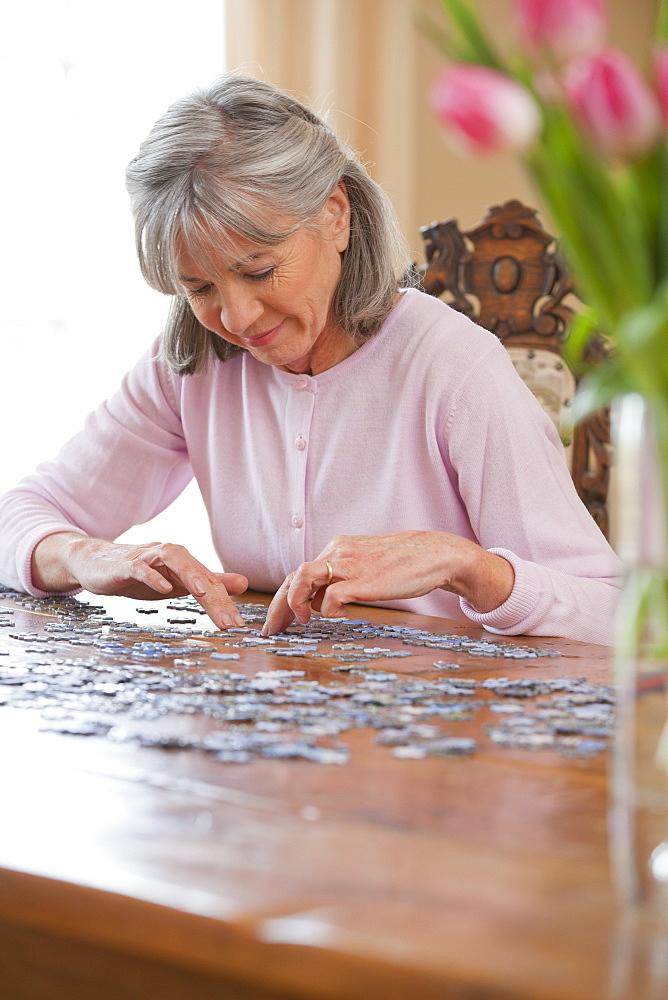 Smiling senior woman assembling jigsaw puzzle on table