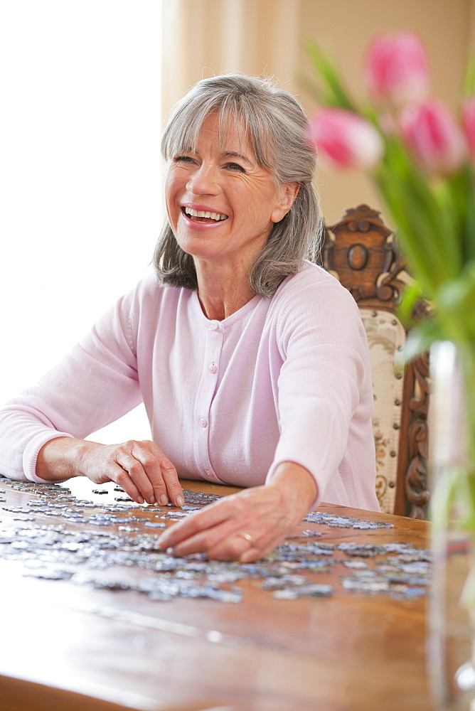 Happy senior woman assembling jigsaw puzzle on table