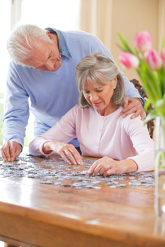 Senior couple assembling jigsaw puzzle on table