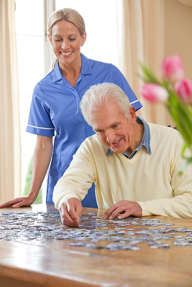 Home caregiver watching senior man assemble jigsaw puzzle on table