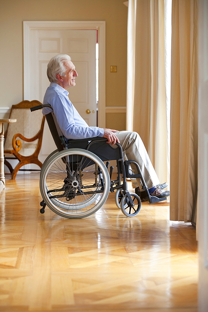 Smiling senior man sitting in wheelchair and looking out window