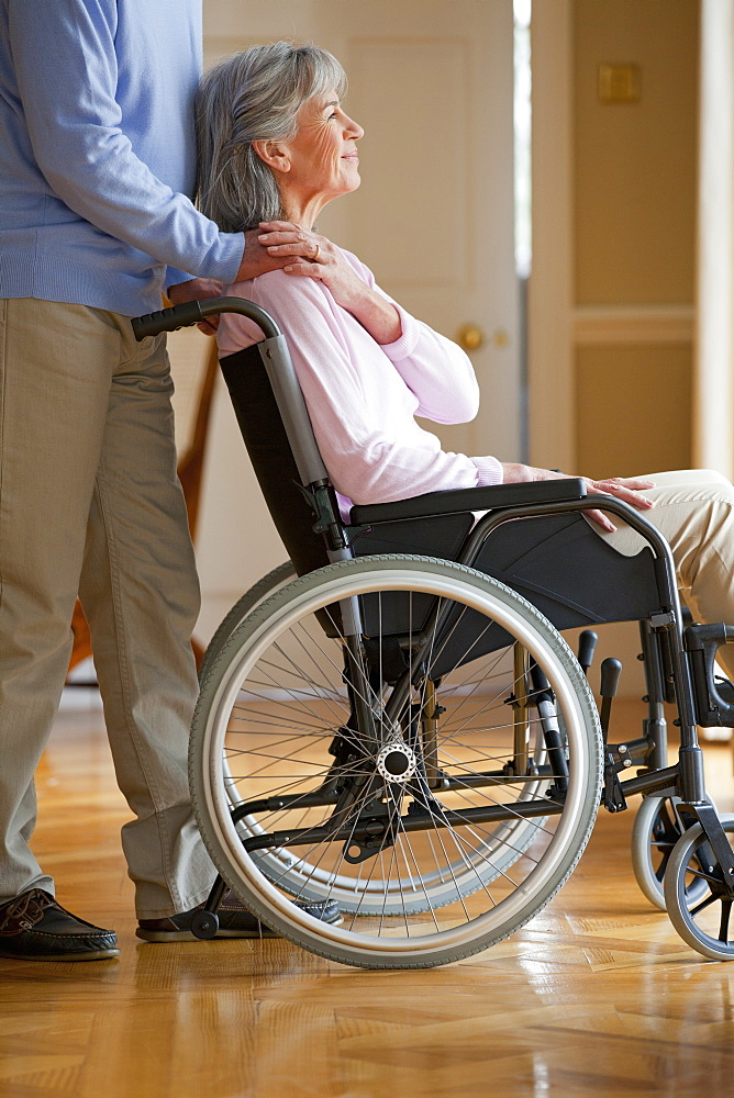 Senior man holding hands with senior woman in wheelchair