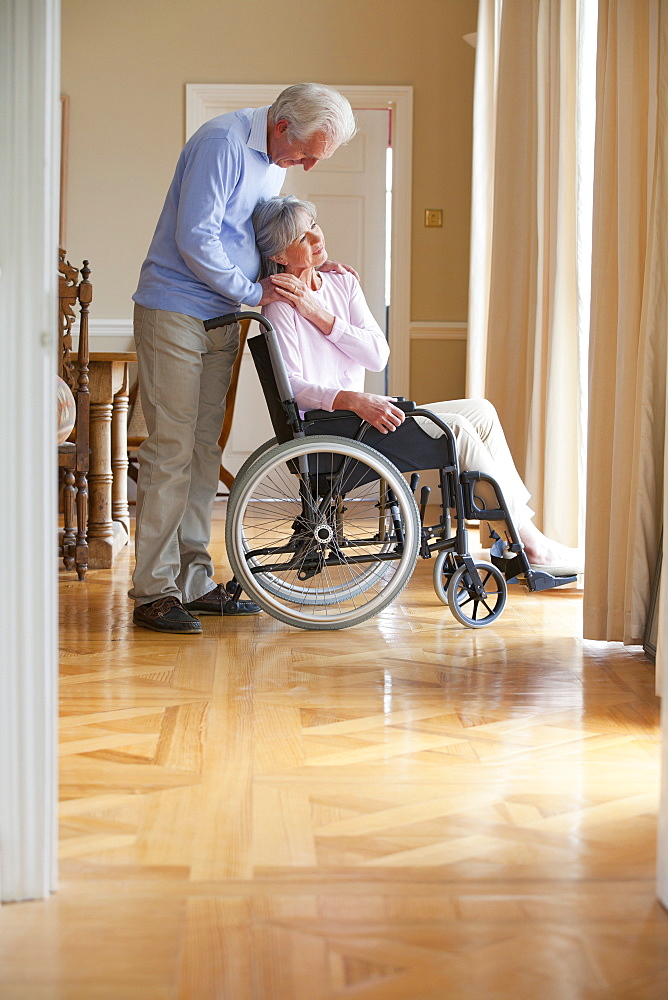 Senior man hugging and holding hands with senior woman in wheelchair at window