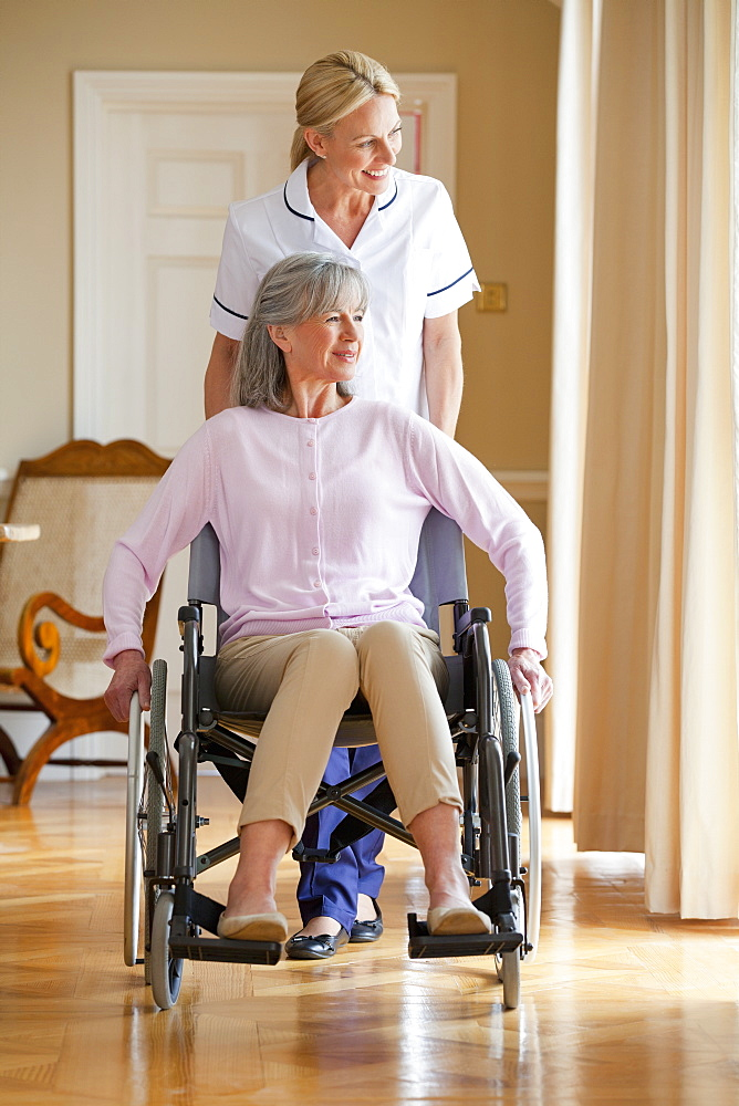 Smiling home caregiver pushing senior woman in wheelchair