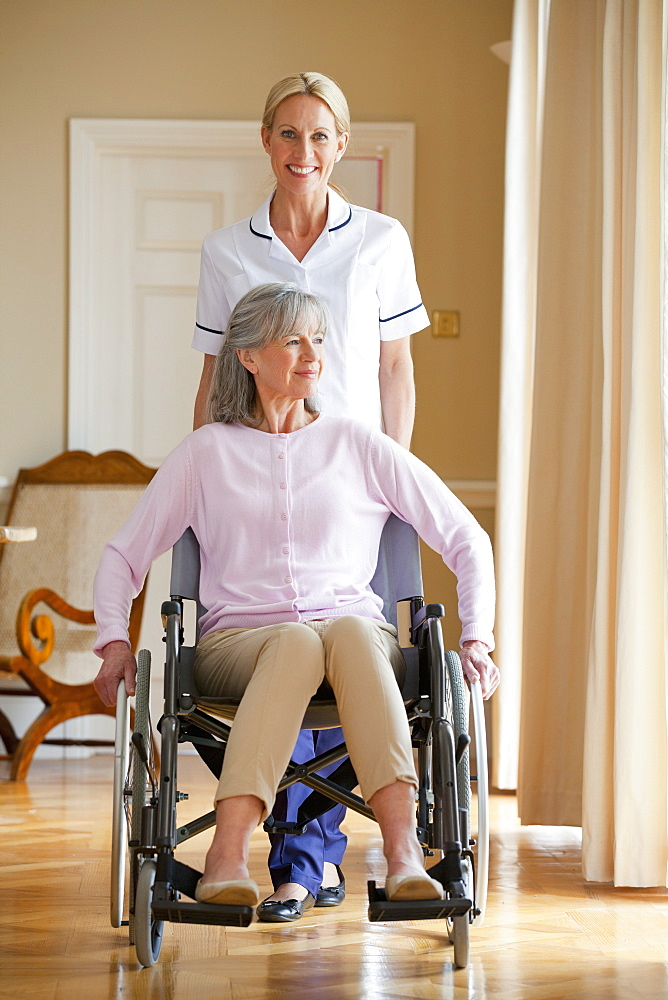 Portrait of smiling home caregiver pushing senior woman in wheelchair